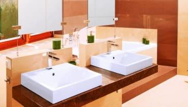 Łazienka 1. Wannę na podeście przesłaniają dwie ścianki podtrzymujące blat z umywalkami oraz lustra, które zamocowano na stalowych linkach rozpiętych pomiędzy ściankami a sufitem. W strefie kąpielowej przeważają brązowe płytki, w pozostałych - beżowe.