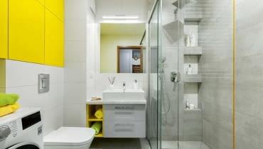 Wnękowe półki w kabinie prysznicowej celowo rozmieszczono na różnej wysokości - dzięki temu mogą z nich wygodnie korzystać i duzi, i mali. Warto dodać, że takie półki są bezpieczne i dla domowników (nie uderzą się o wystające elementy), i dla ustawionych na nich kosmetyków (nie spadną na podłogę). Na podłodze położono gresowe płytki Timbre Grey, na ścianach - Timbre White i Timbre cement; przy kabinie wkomponowano szklaną listwę Yellow (wszystko z firmy Tubądzin).