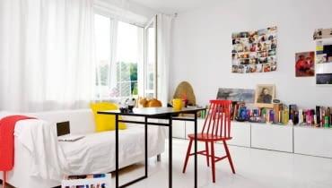 Wszechobecna biel powiększa optycznie małe mieszkanie (38 m kw.). Blaty szafek (takie same wiszą w kuchni) pełnią funkcję biblioteczki i miejsca na bibeloty i zdjęcia. Na podłodze - malowane deski. Kotka Sissy, trzeci domownik, puszy się na oparciu kanapy.