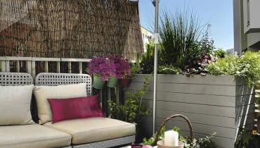 Kącik do relaksu - od strony chodnika przed wzrokiem przechodniów chroni mata i wysoka skrzynia dla roślin. W upały cień zapewnia jasny parasol.