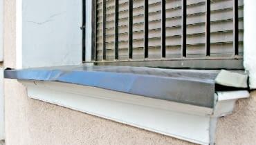 Blaszany parapet zniekształcony przez wysoką temperaturę