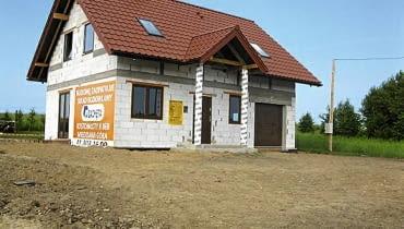 Dom ulokowany jest w odległości 4 m od płotu z jednej strony i niewiele większej z drugiej. Teren dokoła jest pusty i płaski, a wejście zwrócone na południe.