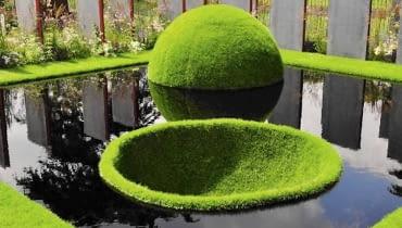 Trawnik jak zielona wyspa. Półkula i misa to aranżacja tylko na pokaz, ponieważ trudno utrzymać ją w takim stanie przez dłuższy czas. Była atrakcją brytyjskiej wystawy Hampton Court Palace Flower Show w 2011 roku