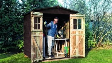 Drewniany domek na narzędzia (180×180 cm), zdwuskrzydłowymi drzwiami idwuspadowym daszkiem krytym papą. Ok. 1200 zł, Castorama