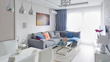 Pokój dzienny połączony z kuchnią to serce domu. Na narożnej kanapie (z firmy Rafek) zmieszczą się nie tylko domownicy, ale i goście. We wnętrzu Julita połączyła nowoczesność z elementami glamour. Meble i dodatki o błyszczących powierzchniach odbijają światło, dodatkowo rozjaśniając pomieszczenie dobrze oświetlone lampami (marki Azzardo).