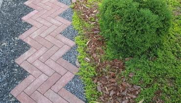 Nawierzchnię dróżek można pokryć brukową kostką klinkierową, betonową, kamienną, brukiem drewnianym, żwirem lub tłuczniem