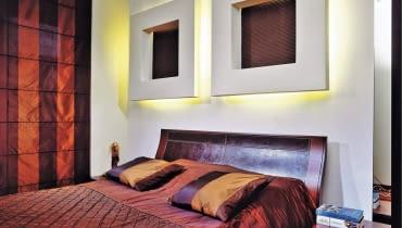 Łóżko stoi na ogół przy najbardziej widocznej ścianie w sypialni. Żal byłoby jej nie wykorzystać - do celów praktycznych albo dekoracyjnych, a najlepiej do obu jednocześnie. Zobaczcie, jak z głową zaaranżować miejsce za głową. <BR > Aranżacje wnętrz. W ramach ozdoby. Oryginalną dekoracją ściany są tu dwie grube ramy z płyty gipsowo-kartonowej. Ich środki wykończono tynkiem strukturalnym pomalowanym farbą w takim samym odcieniu jak meble i dodatki. Te nietypowe konstrukcje posłużyły również do ukrycia oświetlenia zastępującego gospodarzom lampki nocne.