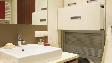 Pralkę przesłaniają drzwi z aluminiowych żaluzji. Nad nią we wnęce znajdują się szuflady i szafka z płyty MDF zamykana drzwiczkami.