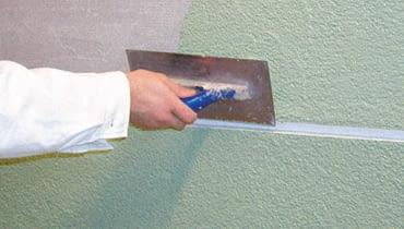 Nanoszenie tynku cienkowarstwowego w kolorze zielonym na ścianę pomiędzy boniami