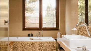 <B> Pojedynczy nie zdziała we wnętrzu wiele, ale w grupie zyskuje moc - ożywia kolorystykę, podkreśla kształt mebli i urządzeń, zdobi. W łazienkach nastał czas mozaiki. </B><BR /> WNĘTRZA: Gospodarze wykończyli mozaiką obudowę wanny oraz ścianę przy umywalce i w kabinie prysznicowej, a więc miejsca najbardziej narażone na kontakt z wodą (wybrano produkt z polerowanego marmuru Emperador włoskiej firmy Sicis). W ten sposób wizualnie podkreślono też strefy mycia i kąpieli. Oprócz mozaiki w łazience zastosowano gres imitujący polerowany trawertyn (płytki 30 x 90 cm i 60 x 90 cm układane na przemian). Odcienie kamienia idealnie pasują do kolorystyki całego wnętrza - na kostkach powtarzają się barwy pozostałych elementów wyposażenia (biel ceramiki, brąz mebli i dodatków, beż gresu). Ciepłe odcienie budują klimat sprzyjający odpoczynkowi. Lustro nad umywalką od góry i od dołu otaczają pasy mozaiki tworzące rodzaj ramy. Do wanny dobudowano schodek wykończony (tak jak cała podłoga) płytami gresu imitującego polerowany trawertyn. W podwieszonym suficie zainstalowano halogeny - dzięki temu można było zrezygnować ze światła sufitowego o dużej mocy i zawiesić jedynie ozdobną lampkę.