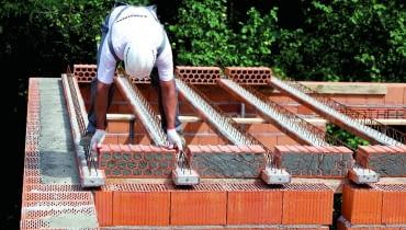 Układanie stropu ceramicznego, etap 3. Drążenia czołowych powierzchni pustaków skrajnych (układanych jako pierwsze) zamyka się zaprawą.