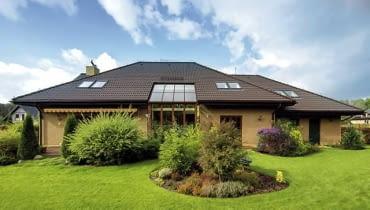 Wielkie przeszklenie pełni funkcję ogrodu zimowego, o którym marzyła właścicielka. Dzięki niemu promienie słońca penetrują wnętrza części dziennej domu na parterze i docierają także na antresolę