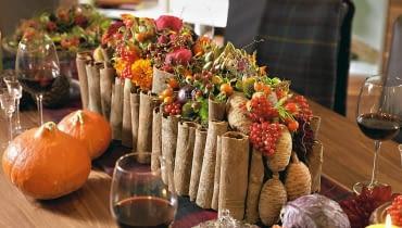 Kompozycje kwiatowe. Stroik w angielskim stylu. W otoczce z cynamonowej kory ozdobionej cedrowymi szyszkami - zwarta kompozycja z dalii, róż, aksamitek, krokosmii, owoców karczocha, róży, granatu, kaliny