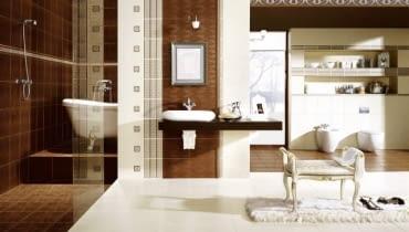 Część ścian wyłożono płytkami z roślinnym wzorem. Stylizowana wanna i nablatowa umywalka podkreślają styl łazienki.