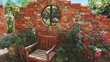 Ogrodowa klasyka - ścianka z cegły. Aby nie zamykała widoku na ogród, pozostawiono w niej otwór na okno.