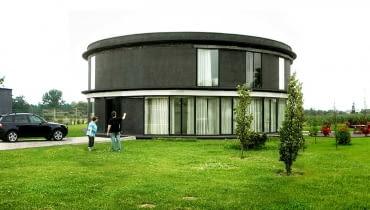 Dom jednorodzinny w Mikołowie: tak jak pozostałe budynki, także dom jednorodzinny jest cylindrem, któremu ciągle niestety brakuje wykończeniowej warstwy aluminium na elewacji. (współpraca: Damian Radwański). Projekt budynku powstał w 2004 r.