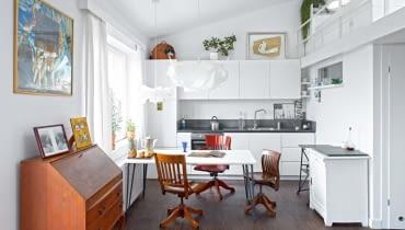 Otwarta kuchnia jest częścią strefy dziennej. Są w niej proste białe szafki (zrobione przez firmę z Mławy) oraz meble, które pasują stylem również do salonu: krzesła biurowe z Ameryki i biała szafka z targu staroci. Na podłodze - dąb olejowany. Blat i pas kamienia na ścianie to chiński granit. Sposób na oszczędności: stół to pomalowana na biało płyta OSB, do której przykręcono metalowe nogi z dawnego biurka córki.