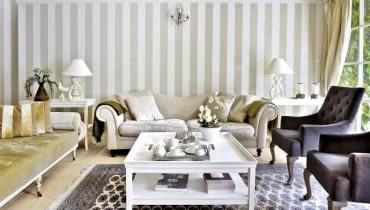 Ścianę pomalowano w szerokie szaro-beżowe pasy (podobny kolor mają obicia niektórych tapicerowanych mebli). Po obu stronach kanapy stoją stoliki pomocnicze; na nich wyeksponowano dekoracyjne przedmioty.