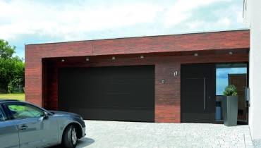 Brama garażowa i drzwi, umieszczone na elewacji blisko siebie, utrzymane są w tym samym stylu i kolorystyce