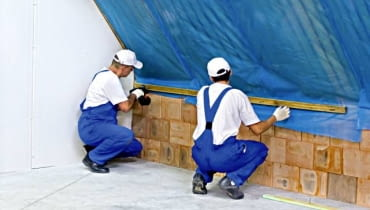 Układanie folii paroizolacyjnej. Należy przy tym zadbać o to, by szczelnie połączyć ją z innymi elementami konstrukcji domu - tu ze ścianą szczytową i kolankową