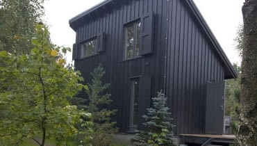 Budynek z jednospadowym dachem i dwoma poziomami mieszkalnymi mieści pokoje sypialne i łazienkę; część dzienna jest obok - w jednoprzestrzennym budynku przekrytym dachem dwuspadowym