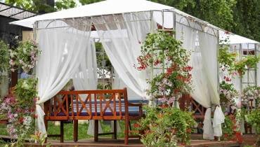 Zadaszony ogrodowy pawilon wsparty na metalowej konstrukcji daje cień ogrodowym biesiadnikom