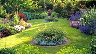 Small country garden with circular island beds and wooden seat