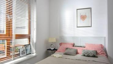 W oknie sypialni, takjakwczęści dziennej, zamontowano białą żaluzję. Wspokojnej aranżacji wnętrza przeważają odcienie beżu ijasnej czerwieni.