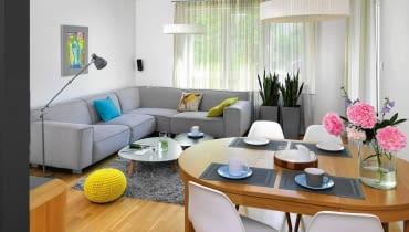 PO ZMIANIE. Narożna kanapa zapewnia komfortowy odpoczynek wszystkim domownikom. Stoliki kawowe mają różną wielkość (niższy można schować pod wyższy). Pokój sprawia teraz wrażenie znacznie większego - to dzięki nowej, jasnej kolorystyce oraz lekkim firanom, którymi zastąpiono ciemne zasłony.
