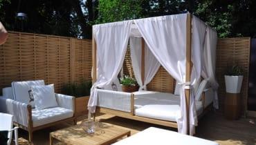 Komfortowe ogrodowe łoże - tkanina rozpięta na drewnianym stelażu chroni nie tylko przed wiatrem, ale też przed komarami.