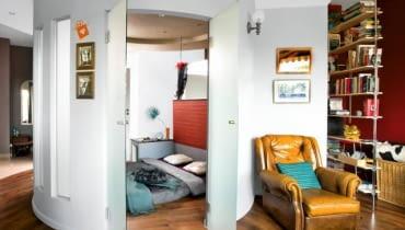W ponadtrzydziestometrowej otwartej przestrzeni dziennej (pokój połączony z kuchnią i przedpokojem) właścicielka postanowiła wydzielić osobną, zamykaną drzwiami sypialnię. Architekt, który podjął się przygotowania projektu, zaproponował rzadko stosowaną konstrukcję na planie koła o średnicy trzech metrów. W aneksie zmieściło się wszystko, co w sypialni niezbędne, łącznie ze schowkiem-garderobą. Z zewnątrz konstrukcja wygląda lekko i nie przytłacza wnętrza. Jest to przede wszystkim zasługa użytych materiałów: w cienkich ściankach z płyt gipsowo-kartonowych umieszczono przeszklenia przypominające okna. Szklane są także dwuskrzydłowe drzwi prowadzące do środka.