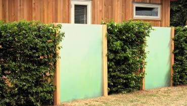Ogrodzenie ze stalowej siatki (skrytej pod gałązkami formowanych krzewów) i tafli z tworzywa sztucznego, imitujących mleczne szkło.