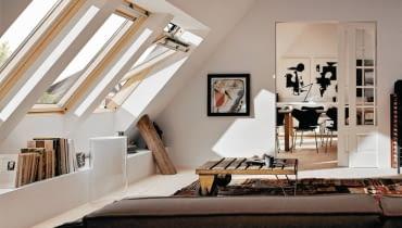 <B> Wnętrza ze skosami mają wiele uroku, często jednak brak nam pomysłu, jak praktycznie zagospodarować kłopotliwe zakamarki pod pochyłym dachem, zwykle z oknem dachowym. Poznajcie nasze propozycje. </B><BR /> Specjalista Justyna Burdow-Gołoś Architekt Wnętrz radzi: <BR /> Aby jak najlepiej wykorzystać przestrzeń pod skosami, warto pamiętać o kilku zasadach. Okna połaciowe dobrze oświetlają wnętrze, gdyż światło wpadające pod kątem i z góry jest bardzo jasne. Standardowa wysokość takich okien wynosi od 80 do 120 centymetrów, ważniejsza jednak jest wysokość, na której są umieszczone. Jeśli będą zbyt nisko, wpuszczą mniej światła, a do tych zamontowanych zbyt wysoko będziemy mieć trudny dostęp, co ma znaczenie przy ich otwieraniu i myciu. Elementy konstrukcyjne (belki, słupy, podciągi) nie powinny być przestawiane ani likwidowane bez uprzedniej konsultacji z fachowcem. Pamiętajmy o tym na etapie planowania przestrzeni. Zamiast zmieniać położenie tych elementów, lepiej wykorzystać je w aranżacji - na przykład obudować zawsze przydatnymi półkami czy szafkami. Skosy sięgające podłogi warto zabudować niską ścianką, przy której łatwiej będzie ustawić meble. W takiej przegrodzie można również zamontować drzwiczki - wtedy przestrzeń za nią stanie się dodatkowym schowkiem. <BR /> ARANŻACJA WNĘTRZ. Podręczna biblioteczka. Wzdłuż ściany z oknami połaciowymi zaprojektowano półkę. Stoją na niej nie tylko ozdobne drobiazgi, ale również książki. Zabudowę zrobiono z płyty gipsowo-kartonowej. Belkę konstrukcyjną pozostawiono odkrytą - taka dekoracja bardzo pasuje do tego wnętrza.