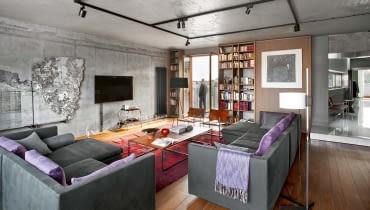 Z salonu do sypialni można przejść przez hol lub dobudowaną podniebną stalową kładką widoczną w głębi po lewej. Biblioteka projektu Katarzyny Kuchejdy; fabryczne oświetlenie skomponowane z lamp do zastosowań ekspozycyjnych (Erco) i profesjonalnego okablowania (THPG).