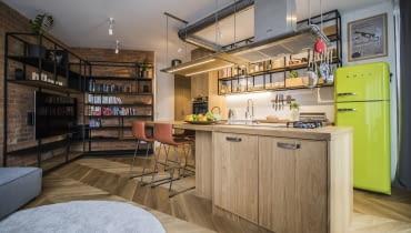Otwarta kuchnia połączona jest z częścią wypoczynkową, którą umownie zaznaczono czerwoną cegłą. Na jej tle okazale prezentują się charakterystyczne dla stylu industrialnego metalowe meble.