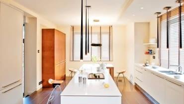 W kuchniach z niską zabudową oświetlenie podszafkowe trzeba zastąpić sufitowym. Modele wybrane do tego wnętrza nie tylko dobrze oświetlają blaty robocze, ale również - ze względu na ciekawą nowoczesną formę - są jego główną ozdobą. Dwa rzędy lamp wiszących, z długimi, przypominającymi sople oprawami z tworzywa sztucznego, zapewniają mocne punktowe oświetlenie miejsc do pracy (na wyspie oraz na blacie pod oknem). Emitowane przez nie światło nie zawsze jest wystarczające w dużej kuchni o powierzchni 28 m kw. Wtedy gospodarze korzystają z halogenów zainstalowanych w częściowo podwieszonym suficie. Oświetlenie wnętrza uzupełnia oryginalna lampa zwieszająca się nad stołem. Fragmenty ścian najbardziej narażone na zabrudzenie obłożono corianem (z tego trwałego i plastycznego materiału są też zrobione blaty).