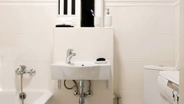 tej mikroskopijnej łazience udało się zmieścić nie tylko wszystkie niezbędne urządzenia, ale także i pralkę. A to dzięki temu, że sedes został zainstalowany w narożniku. Jego skośne ustawienie nie przeszkadza w wygodnym z niego korzystaniu.