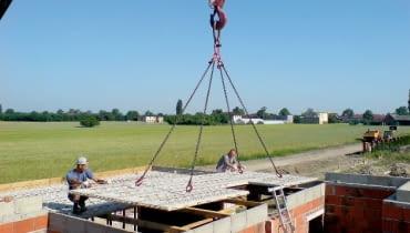 Układanie prefabrykowanej płyty żelbetowej za pomocą dźwigu