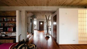 Betonowe sufity, odsłonięte słupy konstrukcyjne i ceglane ściany zmieniły mieszkanie w tradycyjnym szeregowcu w nowoczesne, przestronne wnętrza nawiązujące do stylu loftów. A jednak ten dom jest pozbawiony charakterystycznej dla nich surowości. Pan Robert, właściciel, a zarazem projektant, ocieplił go drewnem, tkaninami i obrazami własnego autorstwa. <BR /> DOM. Łazienka została urządzona w kubiku, na którego suficie chętnie wylegują się domowe koty. Jedną ze ścian częściowo przeszklono luksferami, dzięki czemu do pomieszczenia wpada naturalne światło.