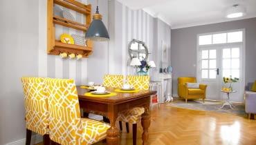 Stylizowany dębowy stół o pięknych toczonych nogach Alina wypatrzyła w sklepie zużywanymi meblami (tam znalazła też szafę dosypialni). Do stołu dobrała krzesła z IKEA, którym sprawiła nowe pokrowce w swoim ulubionym żółtym kolorze. Meble stoją na tle tapety w szerokie pasy (firmy Rasch). W głębi widać salonik, a w nim imitację kominka zrobioną przez stolarza. Przed kominkiem 'wygrzewa' się porcelanowy chart.