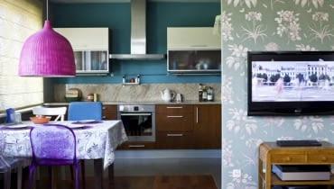 KOLOROWA I WESOŁA. Fantazyjne abażury: z pomalowanej na różowo wikliny oraz z koronki zastąpiły wiszące tu wcześniej lampy o prostych formach. Z kolorystyką wnętrza harmonizuje tapeta w kwiatowy wzór, którą pokryto ścianę przesłaniającą aneks kuchenny.