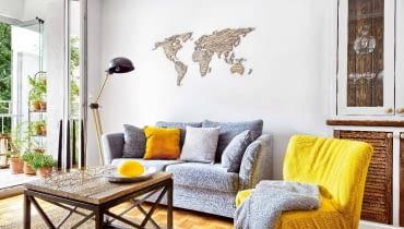 KONTURY KONTYNENTÓW na ścianie nad kanapą zostały wycięte laserem ze sklejki. Wykonawcę tej precyzyjnej roboty gospodarze znaleźli na portalu dawanda.pl; sami pomalowali natomiast sklejkę bejcą - na ten sam kolor co blat stolika kawowego.