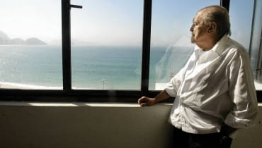 Brazilian architect Oscar Niemeyer looks at the Copacabana beach from his office after his interview with Reuters in Rio de Janeiro, in this June 16, 2003 file photo. Niemeyer, a towering patriarch of modern architecture who shaped the look of contemporary Brazil and whose inventive, curved designs left their mark on cities worldwide, died late on December 5, 2012. He was 104. Niemeyer had been battling kidney and stomach ailments in a Rio de Janeiro hospital since early November. His death was the result of a lung infection developed this week, the hospital said, little more than a week before he would have turned 105. REUTERS/Sergio Moraes/Files (BRAZIL - Tags: OBITUARY SOCIETY)
