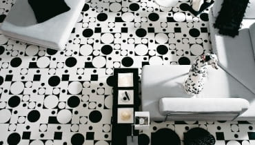Odważna kolorystycznie wykładzina w postaci geometrycznej układanki stanowi tło dla wnętrza konsekwentnie zaprojektowanego w barwach bieli i czerni.