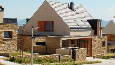 Osiedle domów jednorodzinnych - kamień na parterze, tynk na piętrze i powtarzające się drewniane elementy stolarki okiennej i drzwiowej