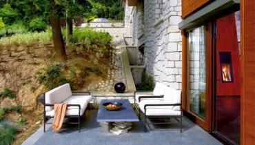 W tym domu dopilnowano, by posadzka wewnątrz i na tarasie była na tym samym poziomie. Wyściełane, wygodne meble nawiązują do tych z wnętrza. Taras osłania skarpa, w którą wkomponowano budynek
