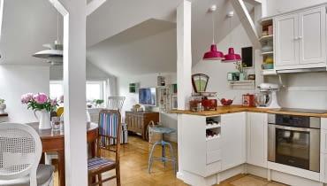 Słupy wyznaczają granicę między aneksem kuchennym a pokojem dziennym. Projektując kuchnię, pani domu zrobiła najpierw spis niezbędnych naczyń i akcesoriów, a następnie policzyła, ile potrzeba szuflad, by je wszystkie pomieścić. Gotowe sosnowe szafki z IKEA pomalowała na biało.