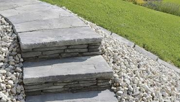 Betonowe płyty do budowy ogrodowych schodów mogą do złudzenia przypominać kamień, np. dekoracyjny łupek lub wapienie