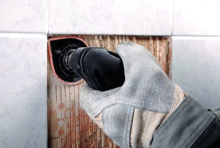 Szpachelką lub innym narzędziem czyścimy ścianę pod usuniętymi płytkami oraz krawędzie sąsiadujących płytek ceramicznych. Potem podłoże i brzegi pozostałych płytek zwilżamy wodą