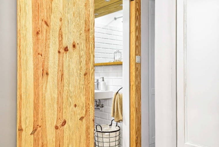WWĄSKIM PRZEJŚCIU nie było miejsca na tradycyjne drzwi do łazienki. Zastąpiono je więc przesuwanymi, które zawieszono na metalowej prowadnicy (zinternetowego sklepu zręcznie kutymi dodatkami). Aby zapewnić cyrkulację powietrza włazience, są zawsze lekko odsunięte.